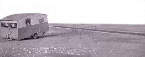 On one occasion in the desert the caravan broke clean away from the Sapphire Here it is resting on the sand with typical desert scenery and the narrow strip of desert road in the background